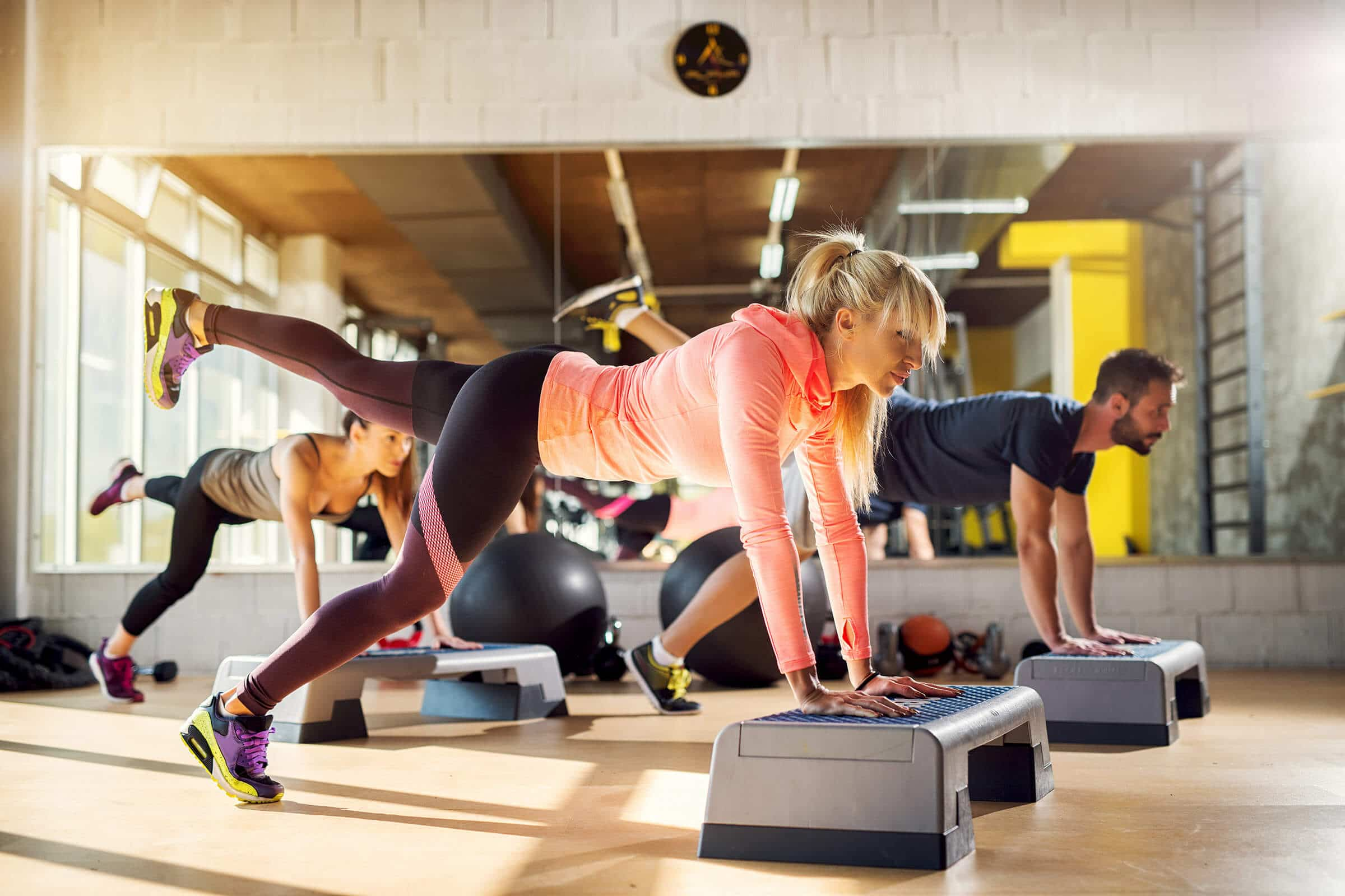 Group of athletes working push ups with one leg up in the air at