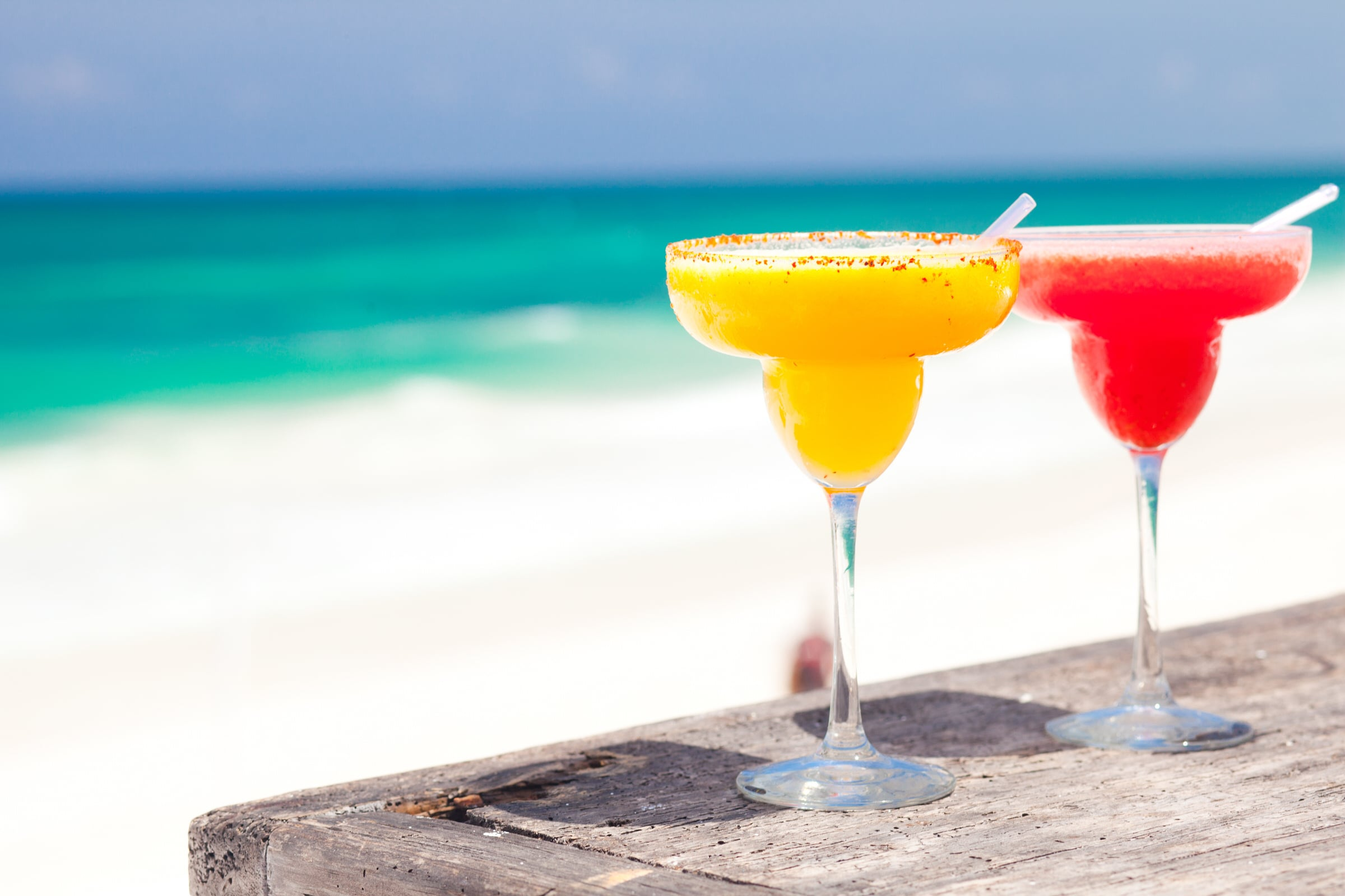 two perfect mango and strawberry margarita, beach background